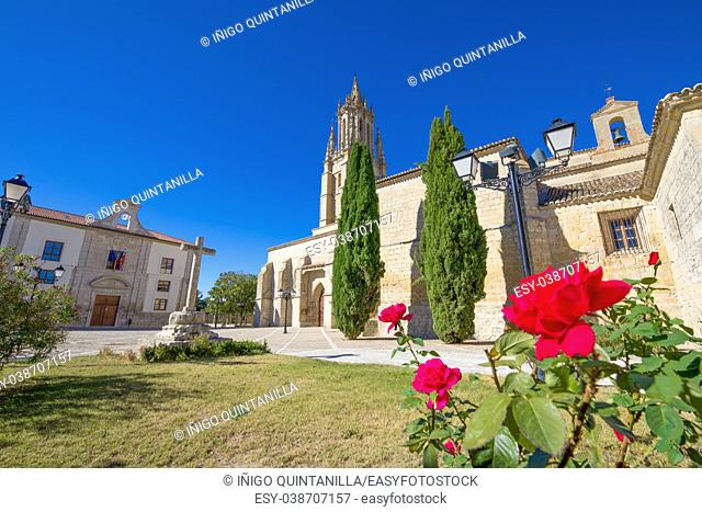 Collegiate of San Miguel, or Saint Michael, monument from eleventh to sixteenth century, ancient stone cross and red flowers in Ampudia village, Palencia