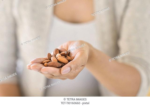 Close-up of woman holding almonds