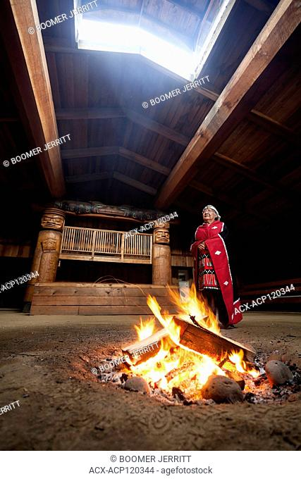 A first nations elder dressed in her traditional regalia stands beside a fire in the bighouse in the village of Oweekeno