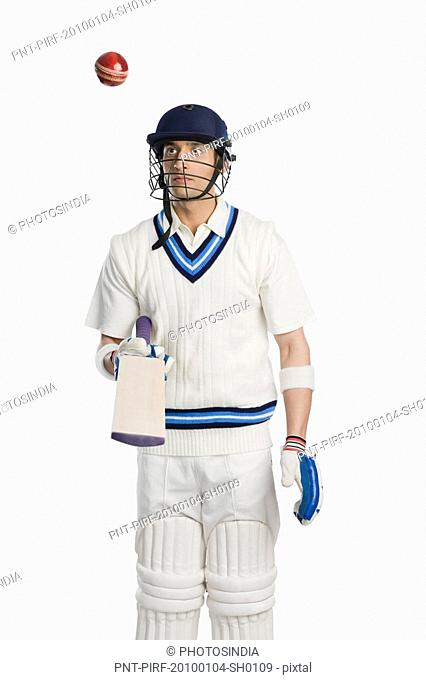 Cricket batsman tossing a ball on a bat