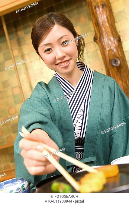 Woman smiling and holding chopsticks, front view, Japan