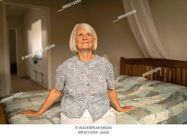 Thoughtful senior woman relaxing on bed