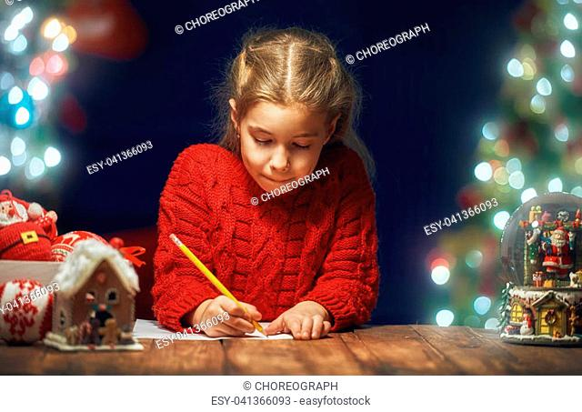 Merry Christmas and Happy Holidays! Cute little child girl is writing the letter to Santa Claus near tree indoors