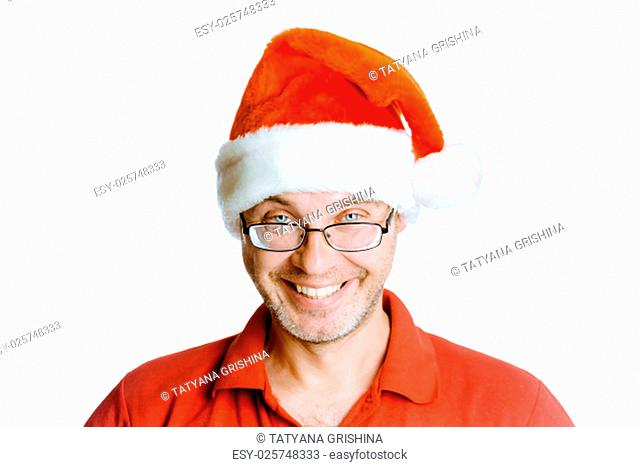 Smiling happy unshaven man on a white background with glasses and a hat Santa