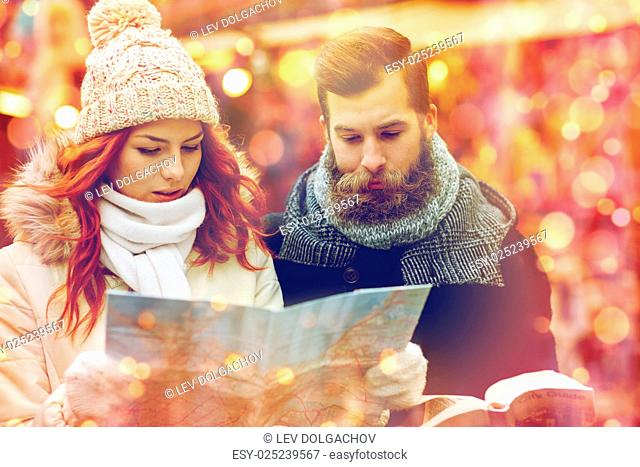 holidays, winter, christmas, tourism and people concept - happy couple in warm clothes with map and city guide in old town