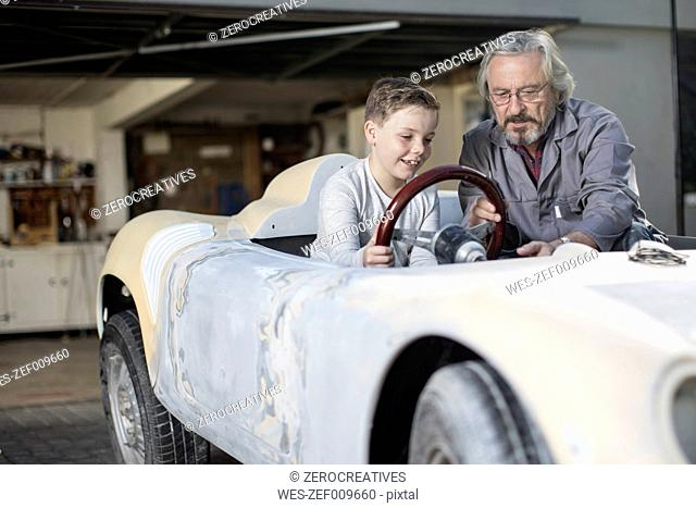Senior man explaining convertible to boy