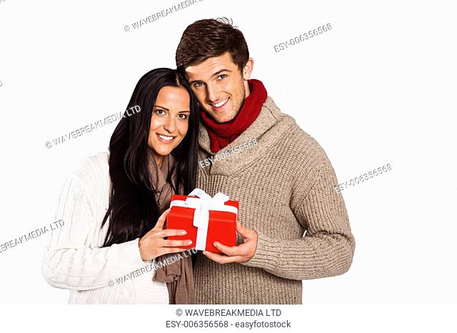 Young couple holding a gift on white background