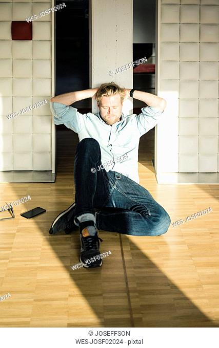 Relaxed businessman in office sitting on the floor leaning against a wall
