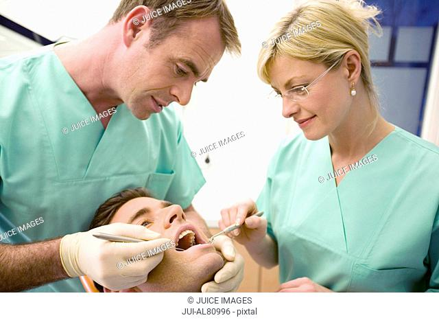 Dentist and assistant treating patient