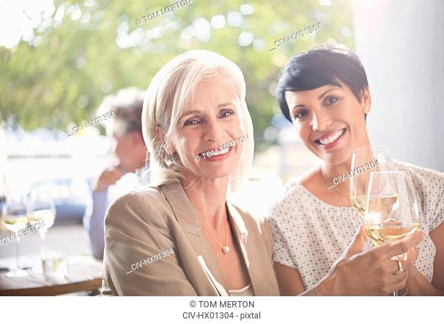 Portrait smiling mother and daughter toasting white wine glasses at sunny restaurant