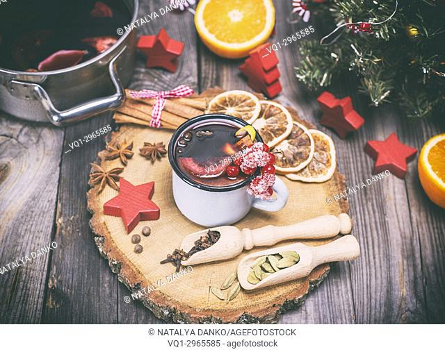 mulled wine in an iron mug and ingredients on a wooden background, vintage toning