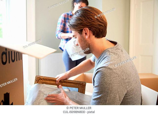 Man packing mirror into cardboard box