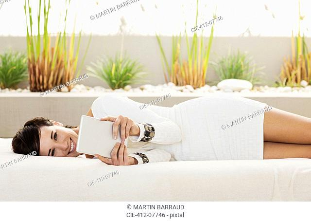 Portrait of smiling woman laying on patio sofa using digital tablet
