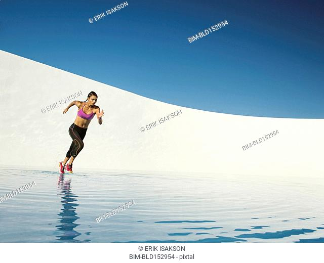 Mixed race woman running on water surface