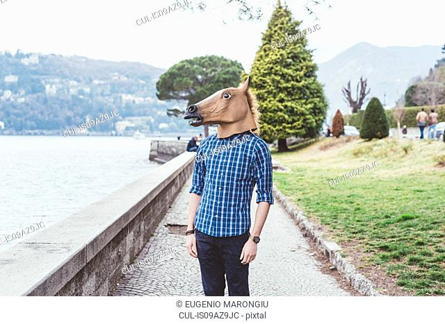 Portrait of man wearing horse mask looking out at Lake Como, Italy