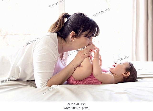 Woman kneeling at bed, playing with baby girl with brown hair wearing pink onesie