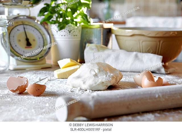 Pizza dough and eggs in messy kitchen