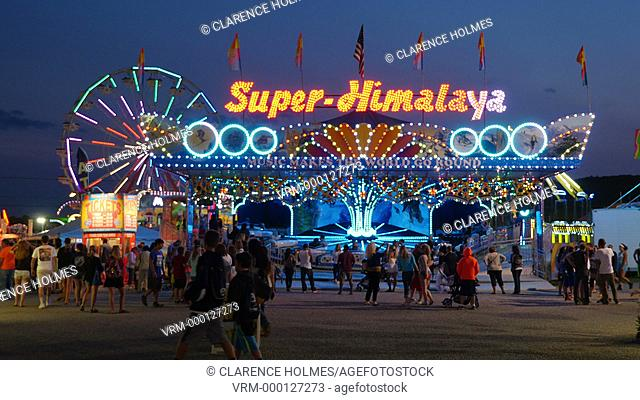 AUGUSTA, NJ - AUGUST 7: The colorfully illuminated Super-Himalaya ride spins with the Gentle Giant Ferris Wheel in the background at twilight sky during the New...