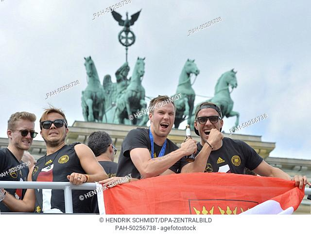 Germany's players Andre Schuerrle (L-R), Mario Goetze, Kevin Großkreutz and Lukas Podolski wave and cheer to the fans as the coach with Germany's national...