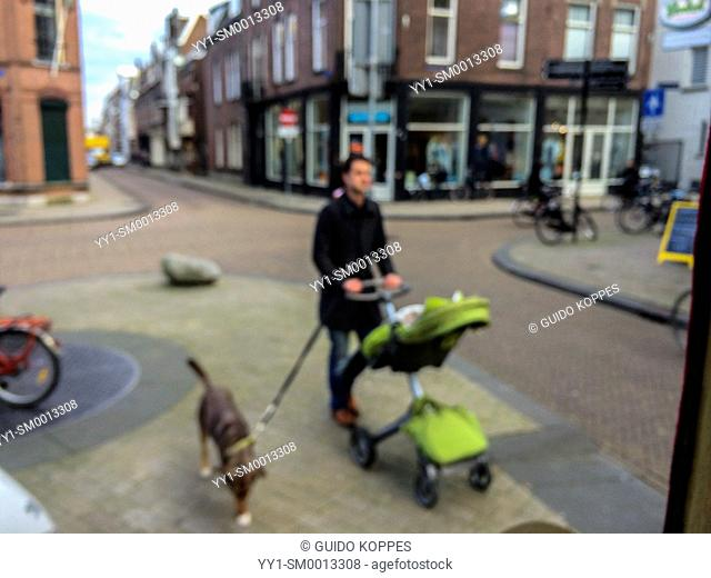 Tilburg, Netherlands. Father with his child in a pushcart, and his dog aside, crossing an intersection down town Tilburg