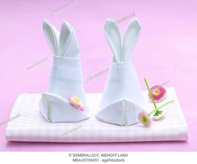 napkins folded like rabbits with flower heads