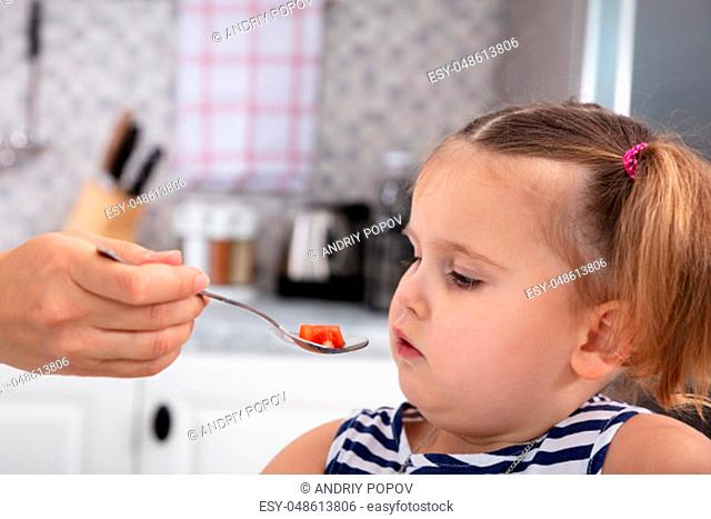 Close-up Of Mother's Hand Feeding Tomato Slice To Her Daughter With Spoon In Kitchen
