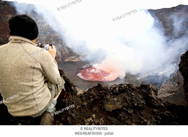 Africa, Democratic Republic of Congo, Virunga National Park, Man sittiing over Nyiragongo volcano crater