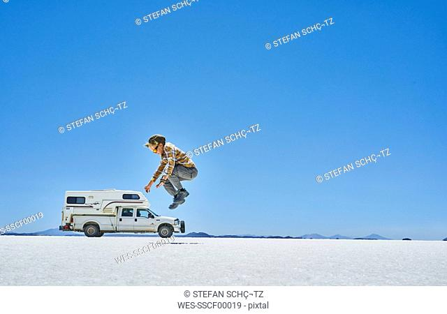 Bolivia, Salar de Uyuni, boy jumping at camper on salt lake
