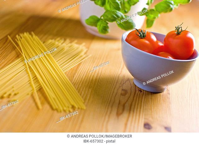 Spaghetti laying beside tomatoes in a bowl with basil