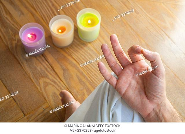 Close view of a man's hand practising yoga, sitting in the lotus position