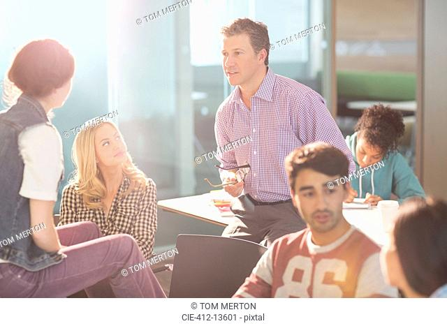 Professor and university students talking in classroom