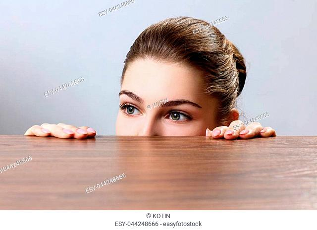 Woman peeping under the edge of wooden table over gray background
