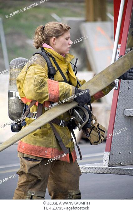Female firefighter removing hose from fire truck, Spokane, Washington