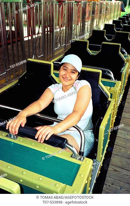 Amusement Park. Latina woman on roller Coaster