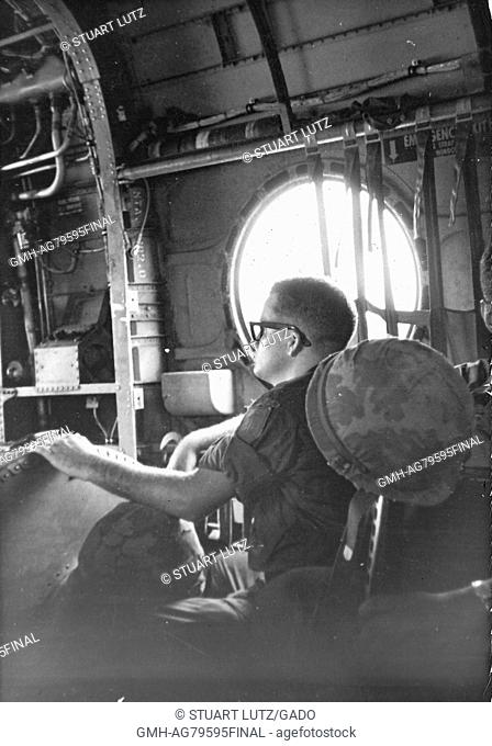 A United States Army serviceman seated near a large window on an airplane, he has his gear between his legs and a helmet hanging from his chair, Vietnam, 1967