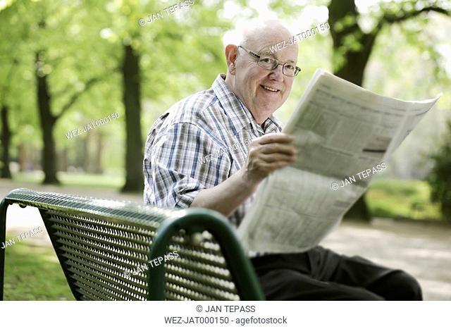 Germany, North Rhine Westphalia, Cologne, Senior man reading newspaper on bench in park