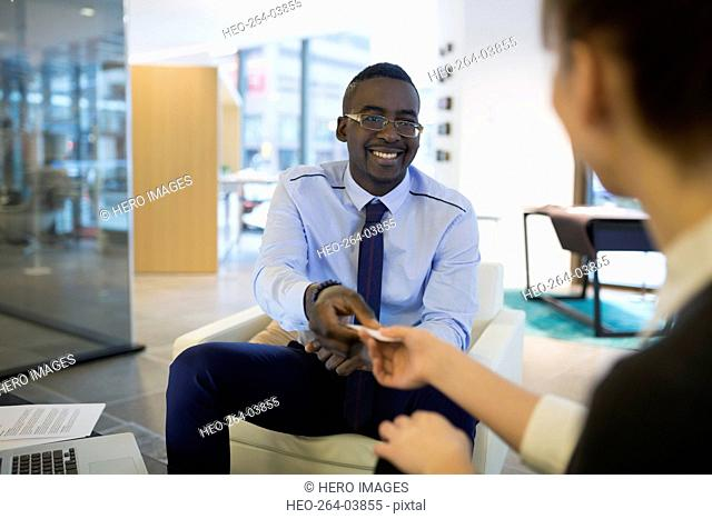 Smiling businessman giving businesswoman business card in lobby