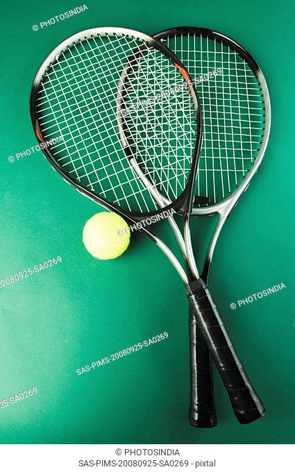 Close-up of two tennis rackets with a tennis ball