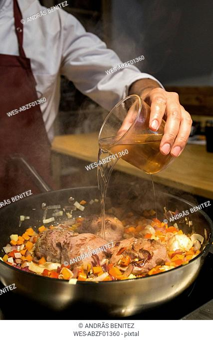 Man pouring a glass of brandy on beef cheeks in a pan with sauteed vegetables