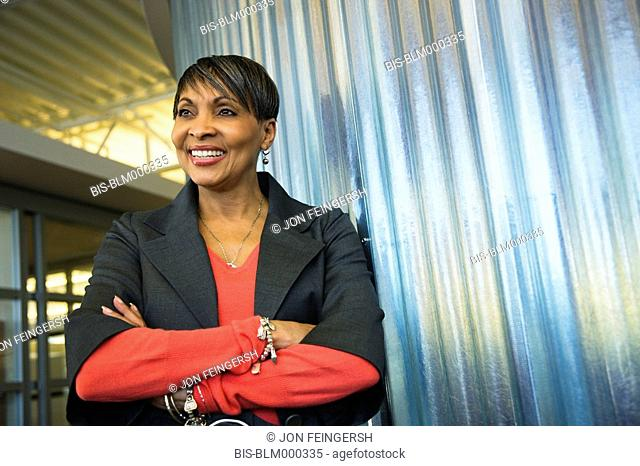 Smiling African businesswoman with arms crossed