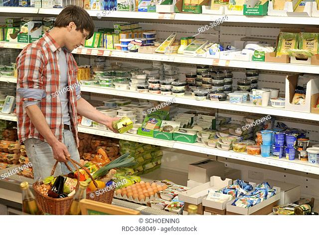 Man in organic grocery store, health food store, wholefood shop, customer, cooling shelf, dairy goods, self-service, Berlin, Germany