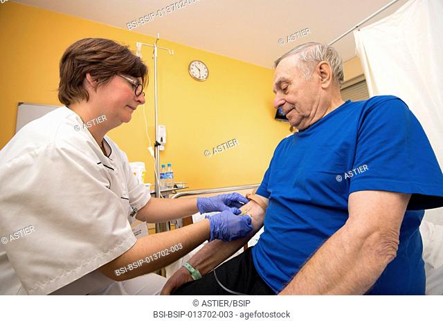 Reportage in the Internal Medecine and Geriatrics service in Saint-Philibert hospital in Lille, France. A nurse takes a blood sample from a patient in his...