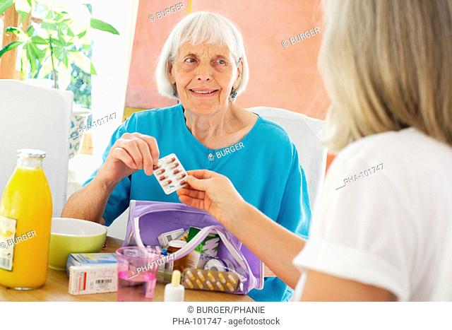 Woman assisting 80 years old woman taking medication