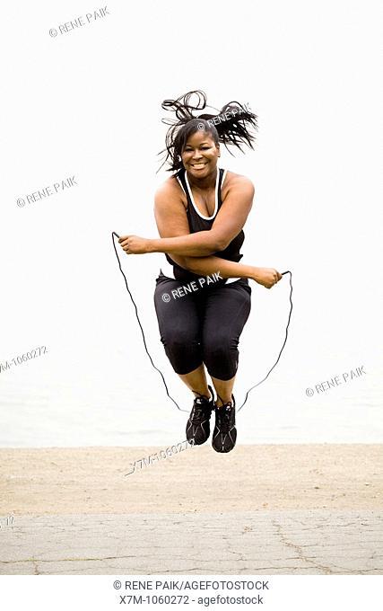 Plus size model jumping rope at a marina park