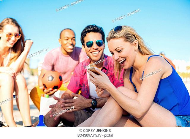 Young woman with friends reading smartphone texts on beach, Santa Monica, California, USA