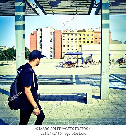 Young man with cap, headphones and backpack walking while watching a terrace and buildings background. Plaça de les Glòries Catalanes, Barcelona, Catalonia