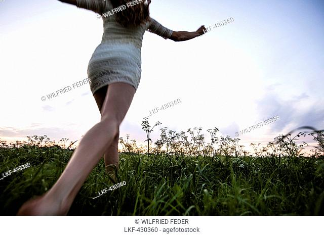 Young woman running over a meadow, Upper Bavaria, Germany
