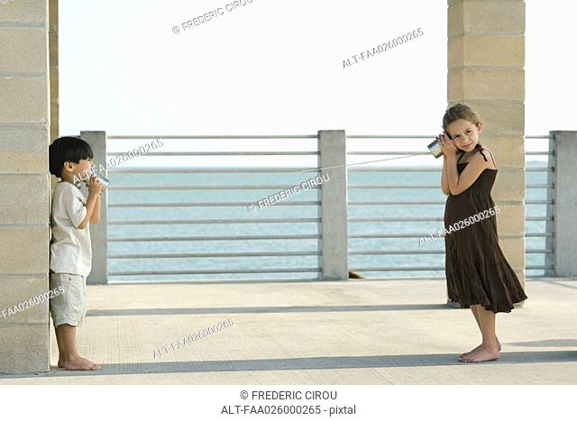 Two young friends playing with tin can phone together, sea in background