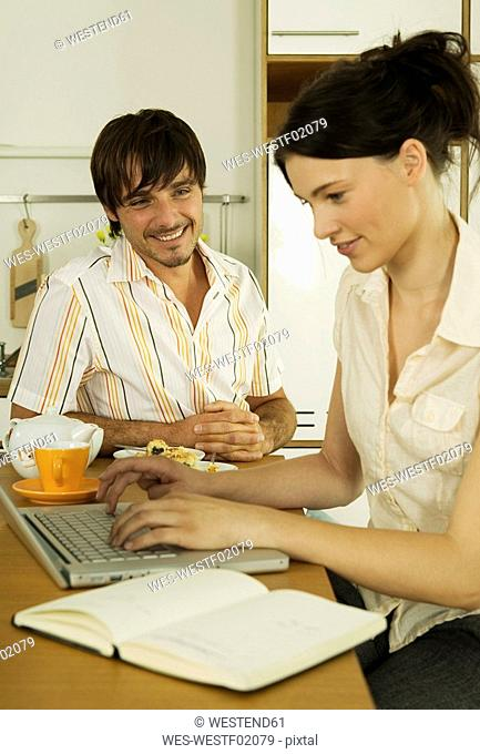 Young couple in kitchen, woman using laptop, smiling