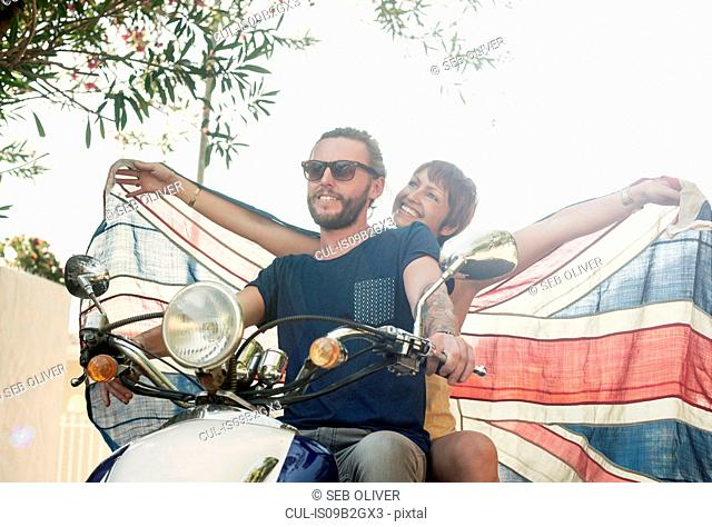 Couple holding up union jack whilst riding on moped, Cape Town, South Africa